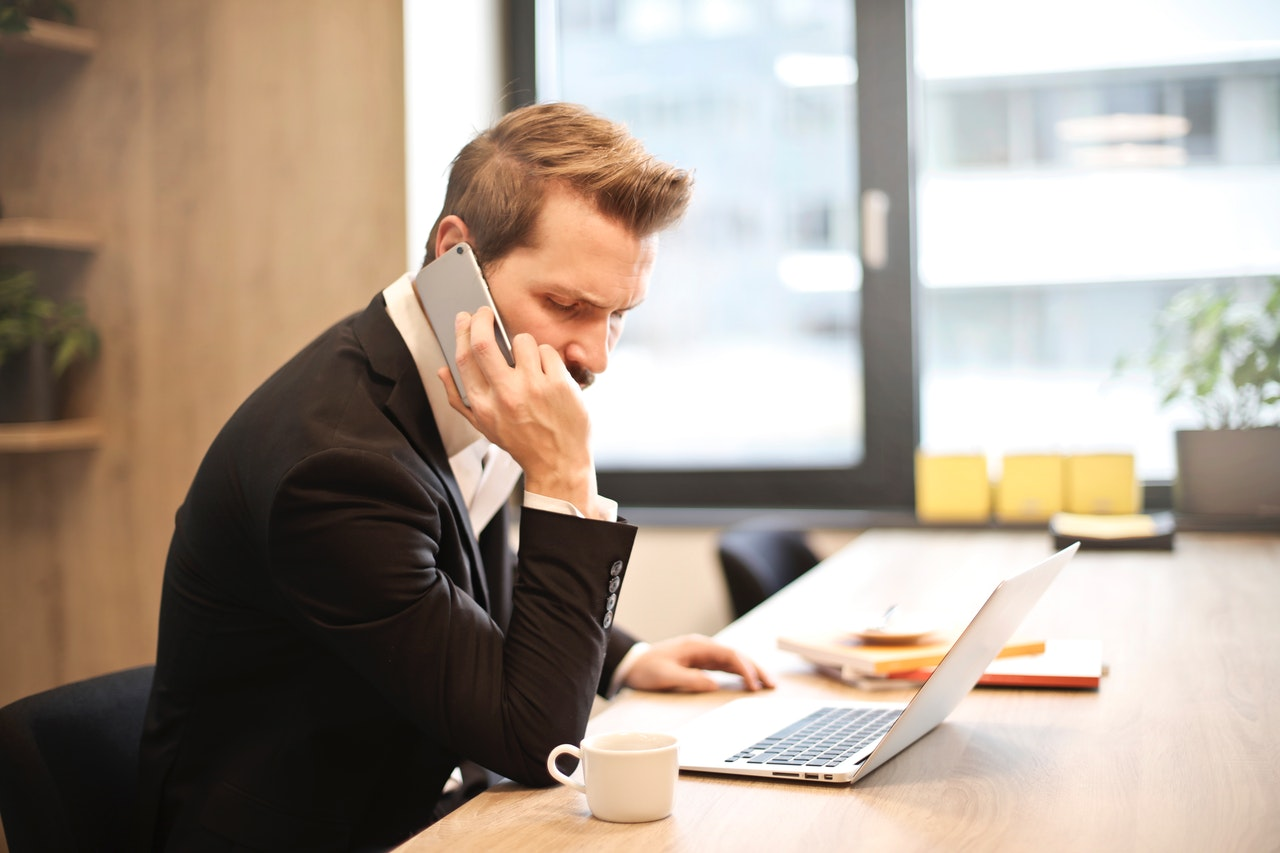 man-having-a-phone-call-in-front-of-a-laptop