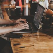 person-in-front-of-laptop-on-brown-wooden-table-asfalistikomarketing