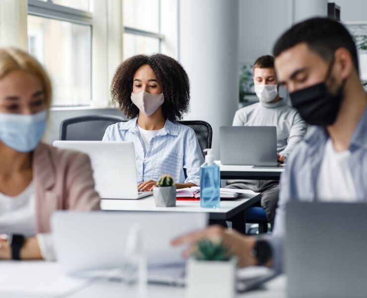 Work with documents and discussion at coronavirus. Guy and woman in protective masks are looking at paper, close up, blurred, focus on african american lady typing on laptop at workplace in office interior