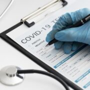 close-up-doctor-completing-covid-medical-form