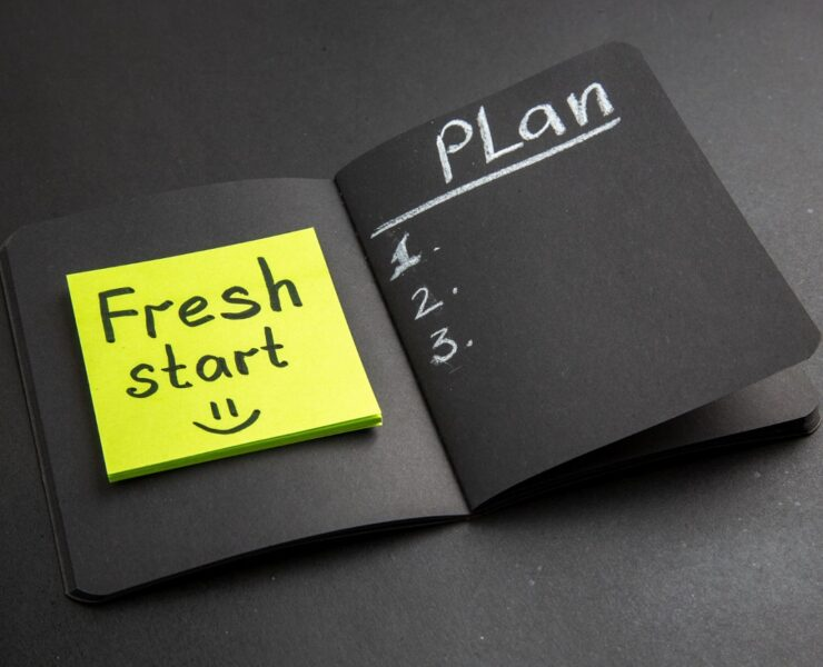 bottom-view-fresh-start-written-sticky-note-plan-written-black-notepad-black-background